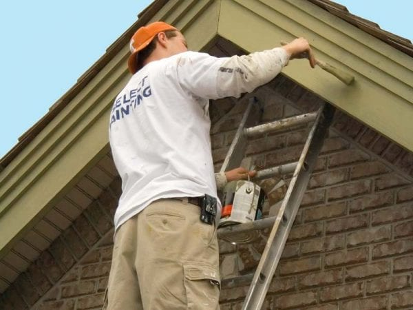 Painting house exterior on a ladder