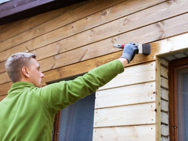 Painting wood exterior for a house with a brush