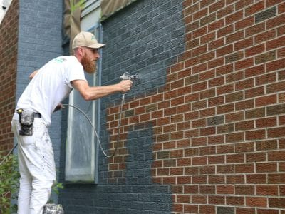 Spray painting a houses brick exterior in Scio Township
