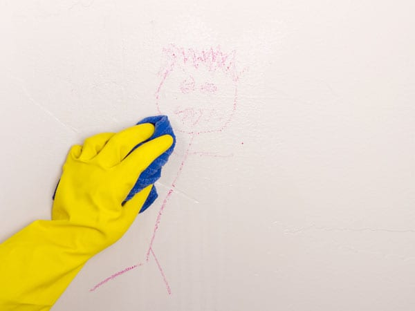 Cleaning kid drawing off a painted wall