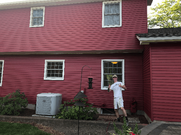 Tribble team member posing with house after painting it red