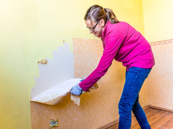 Woman removing wallpaper from wall