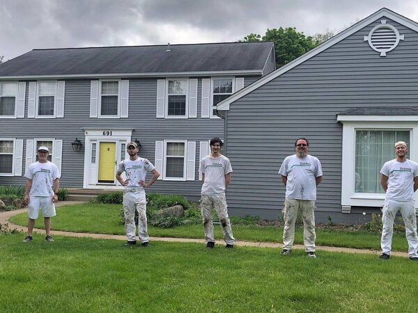 Tribble painting team outside a finished project where they used the best exterior house paint