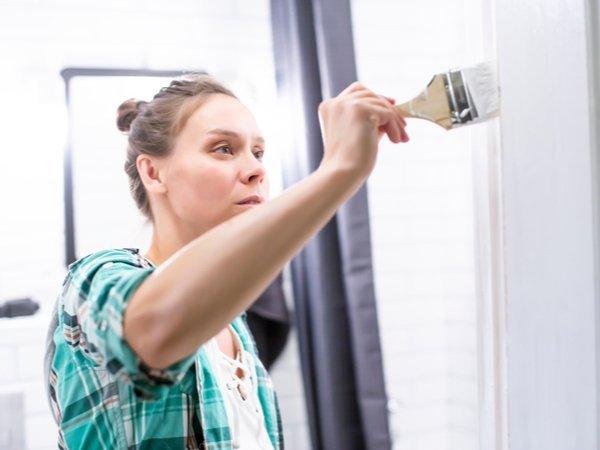 Woman painting a bathroom door